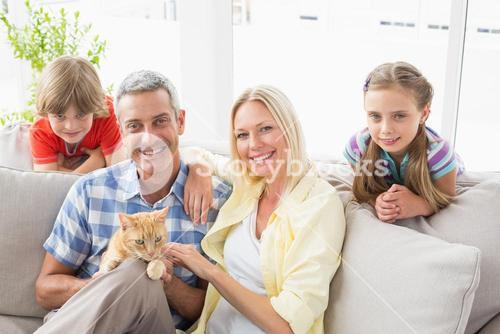 Happy family sitting with cat on sofa at home