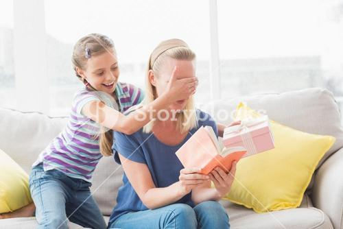 Happy girl surprising her mother with gift at home