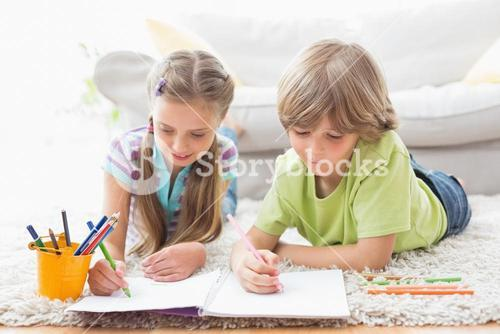 Siblings drawing with colored pencils while lying on rug