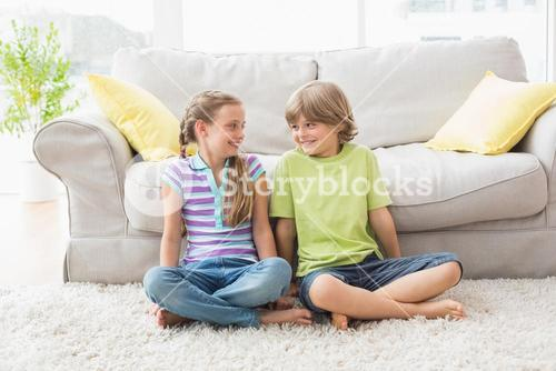 Siblings looking at each other while sitting in liviung room