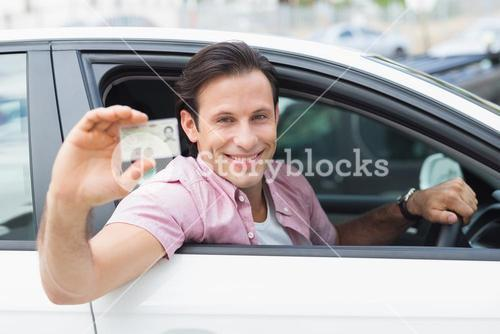 Man smiling and holding his driving license