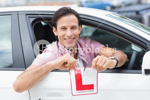 Learner driver smiling and tearing l plate