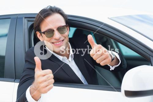 Happy driving businessman with thumbs up