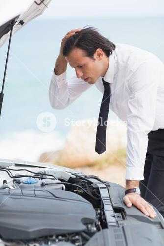 Stressed businessman looking at engine