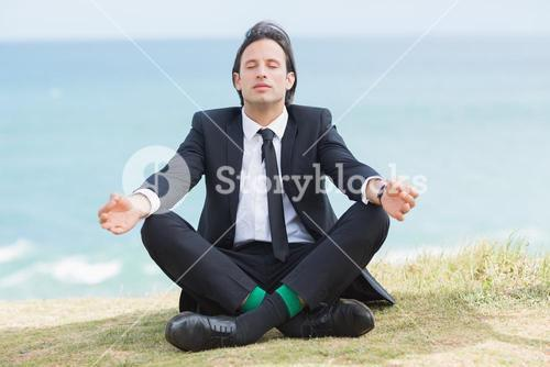 Peaceful businessman sitting in lotus pose relaxing