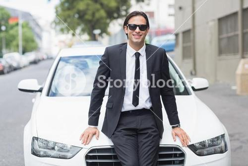 Businessman leaning on the bonnet