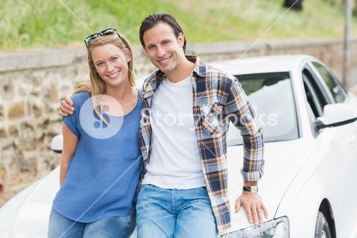 Couple leaning on the bonnet