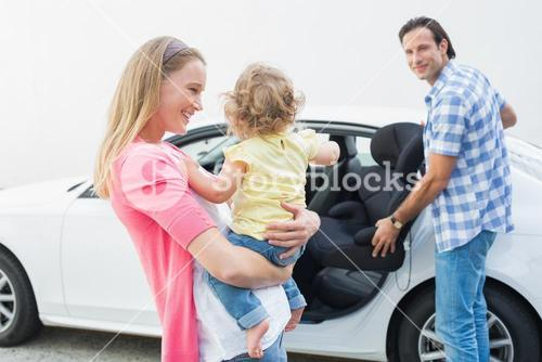 Parents carrying baby and her car seat