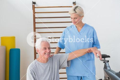 Senior man stretching with his therapist