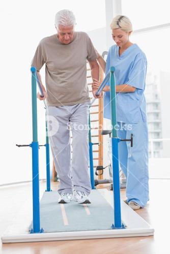 Senior man walking with therapist help