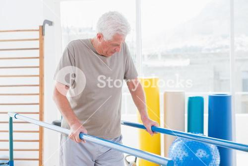 Senior man walking with parallel bars