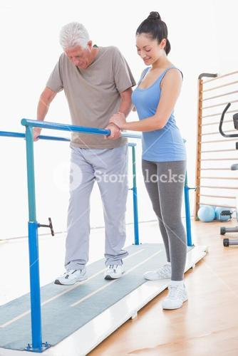 Senior man walking with parallel bars and coach help