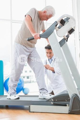 Senior man on treadmill with therapist crouching