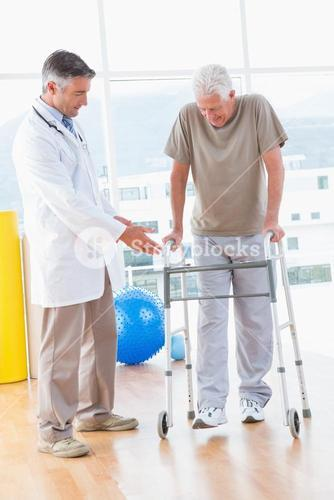 Senior man on zimmer frame with therapist