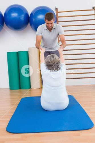 Trainer working with senior woman on exercise mat