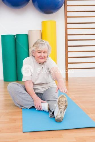 Senior woman working on exercise mat