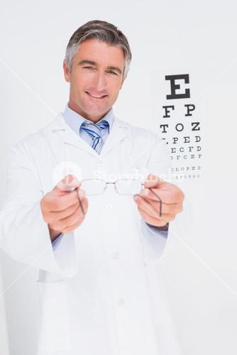 Optometrist holding eyeglasses out
