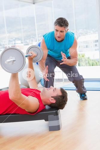 Trainer assisting man with dumbbells