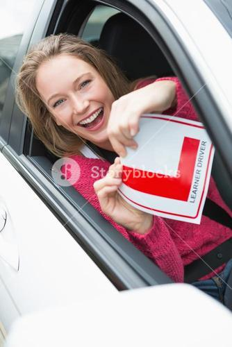 Learner driver smiling and holding l plate