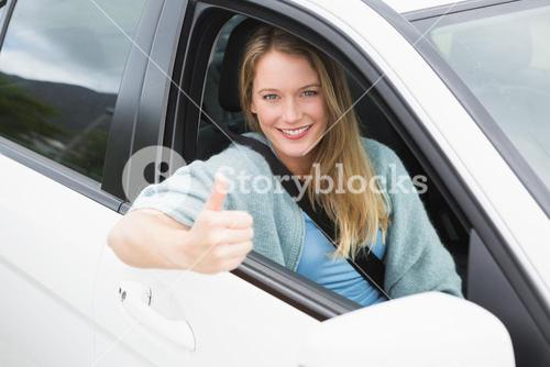 Happy woman sitting in drivers seat thumb up