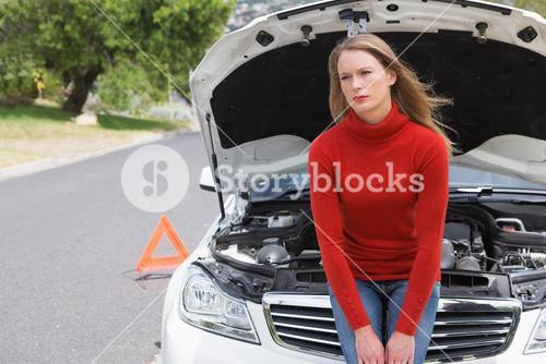 Annoyed young woman beside her broken down car