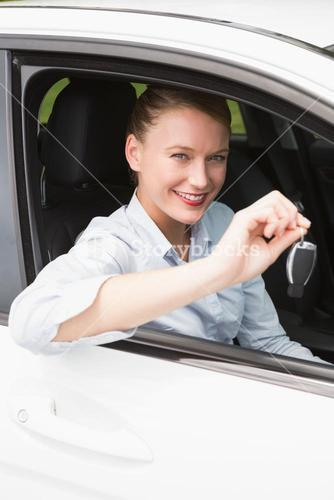 Young businesswoman smiling and holding key