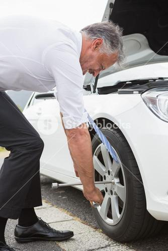 Businessman fixing tire