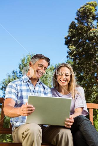 Couple relaxing in the park with laptop