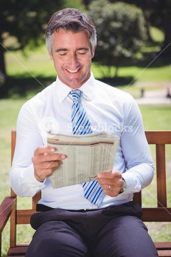 Businessman reading newspaper in the park