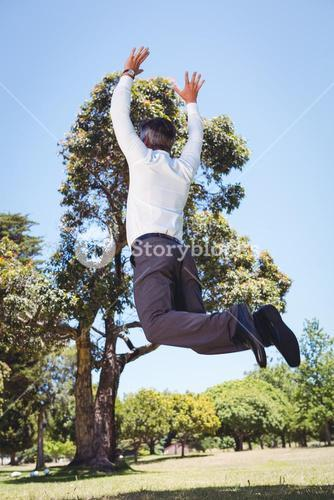 Businessman jumping in the park