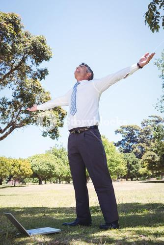 Businessman feeling free in the park