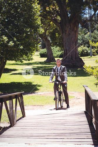 Businessman riding bike in the park