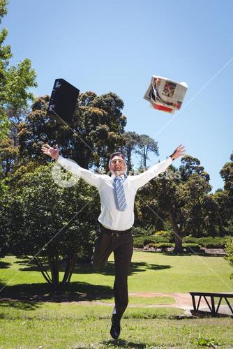 Businessman throwing briefcase and newspaper