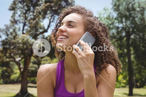 Fit woman on the phone in park