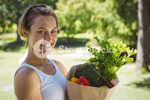 Fit woman with paper bag of vegetables