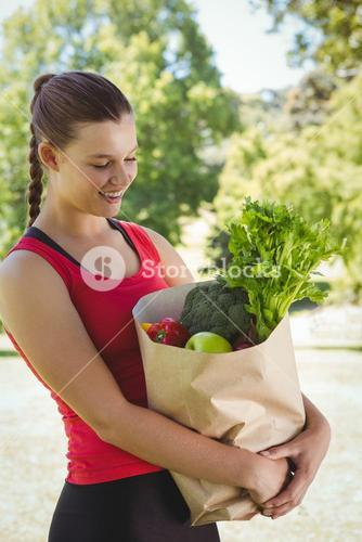 Fit woman holding bag of healthy groceries