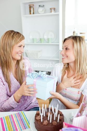 Pleased woman receiving a gift during her birthday party at home