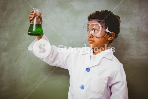 Boy holding conical flask in classroom