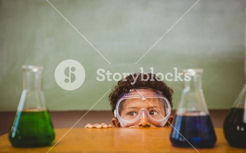 Boy looking at conical flasks in classroom