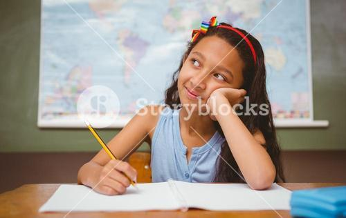 Girl writing book in classroom