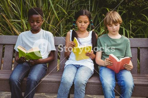 Children reading books at park