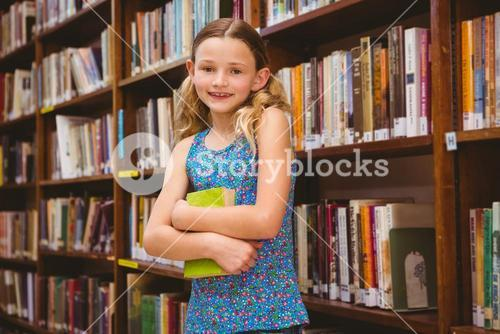 Girl holding book in library