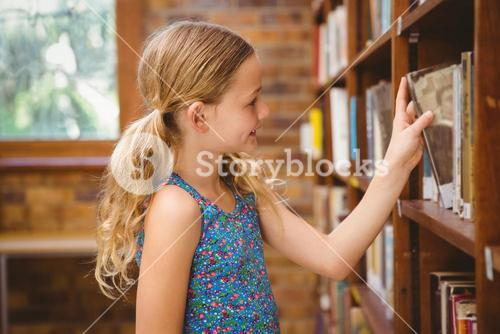 Cute little girl selecting a book