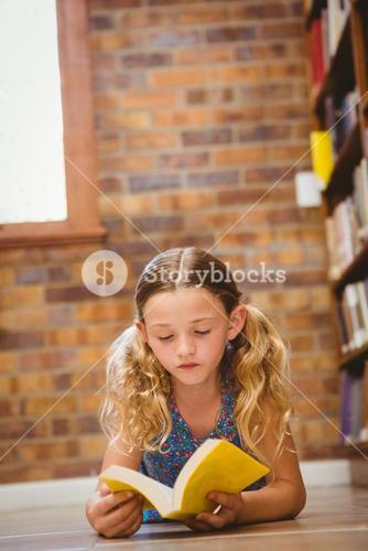 Girl reading book in library