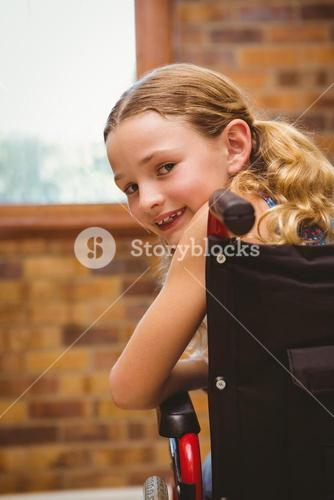 Portrait of cute girl sitting in wheelchair