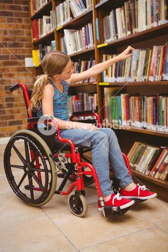 Girl in wheelchair selecting book in library