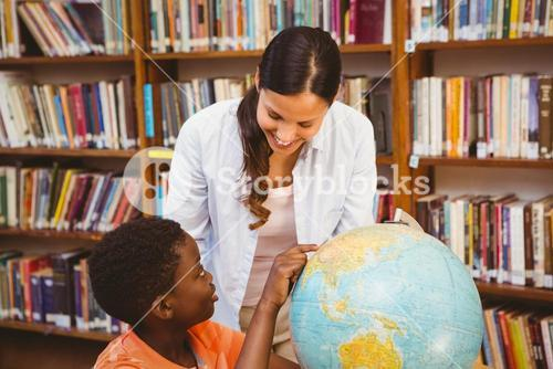 Teacher and boy looking at globe in library