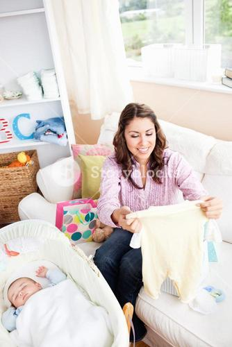 Joyful young mom holding a baby pyjamas sitting in the sofa at home
