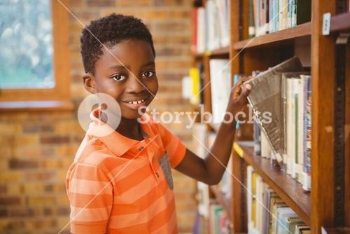 Portrait of boy selecting book in library
