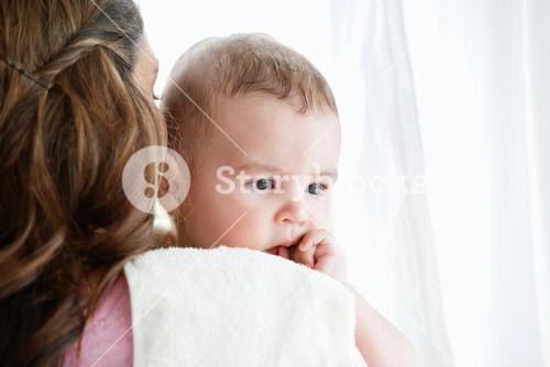 Portrait of a mother pampering her baby after the bath at home